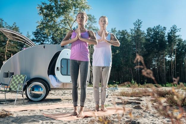 スポーツマット。一緒に朝瞑想しながらスポーツマットの上に立っているスリムでフィット感のある運動カップル