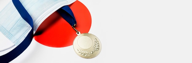 Спортивная медаль рядом с медицинской маской с копией пространства