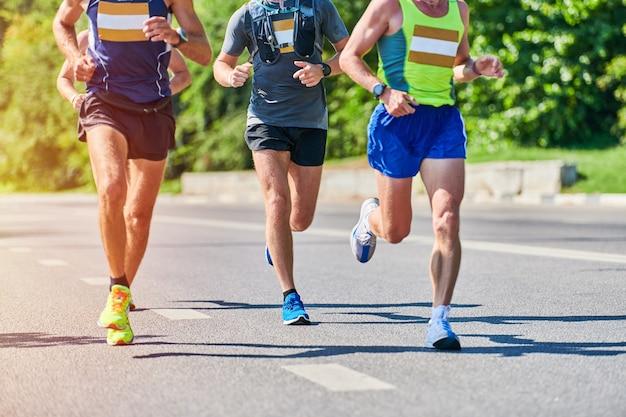 Спортивные мужчины бегают в спортивной одежде на городской дороге