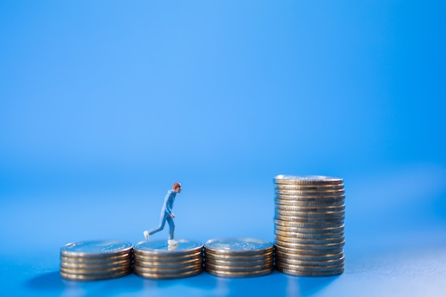 Sport, money and saving concept. closeup of runner miniature figure people run on top of stack of coins on blue background.