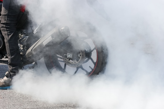 Sport motorbike wheel drifting and smoking on track, background for display