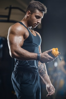 Sport muscular fitness man drinking water after workout