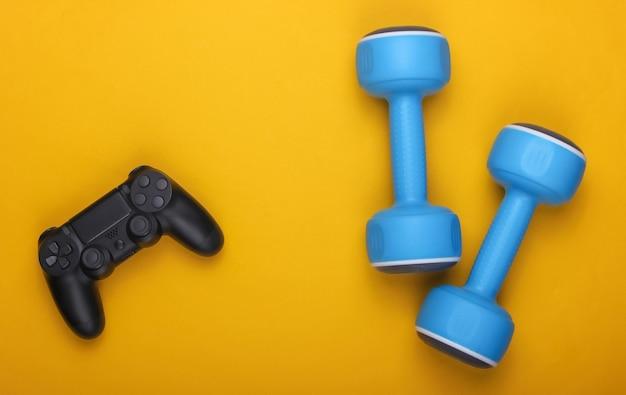 스포츠 또는 엔터테인먼트. 노란색에 게임 패드와 아령