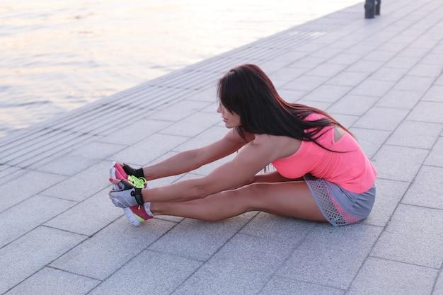 Sport all'aperto, donna che allunga