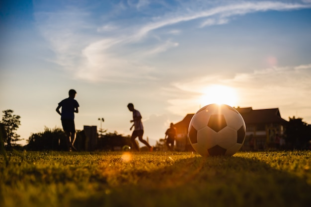 運動のためにサッカーサッカーを楽しんでいる子供たちのグループの屋外スポーツ
