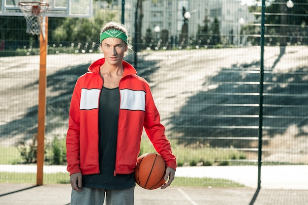 スポーツ衣装。バスケットボールをしに来ている間スポーツジャケットを着ている楽しい青年