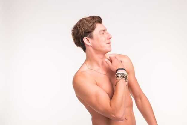 Концепция спорта, людей и эмоций - обнаженный сексуальный мужчина показывает себя и улыбается на белой поверхности с копией пространства
