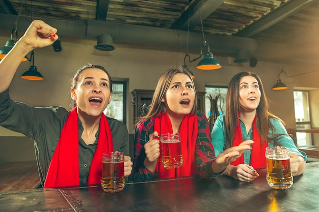 Sport, people, leisure, friendship, entertainment concept - happy female football fans or good young friends drinking beer, celebrating victory at bar or pub. human positive emotions concept
