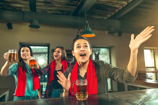 Sport, persone, tempo libero, amicizia, concetto di intrattenimento - tifosi di calcio femminili felici o buoni giovani amici che bevono birra, celebrando la vittoria al bar o al pub. concetto di emozioni positive umane