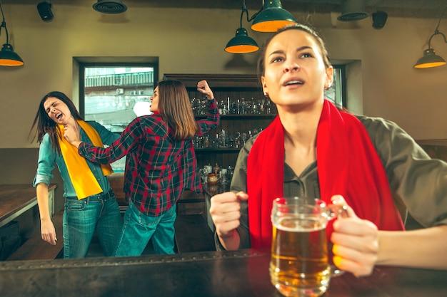 スポーツ、人々、レジャー、友情、エンターテインメントのコンセプト-幸せな女性のサッカーファンやビールを飲み、バーやパブでの勝利を祝う良い若い友人。人間のポジティブな感情の概念