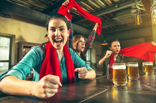 Спорт, люди, досуг, дружба, концепция развлечения - счастливые футбольные фанаты или хорошие молодые друзья пьют пиво, празднуют победу в баре или пабе. концепция человеческих положительных эмоций