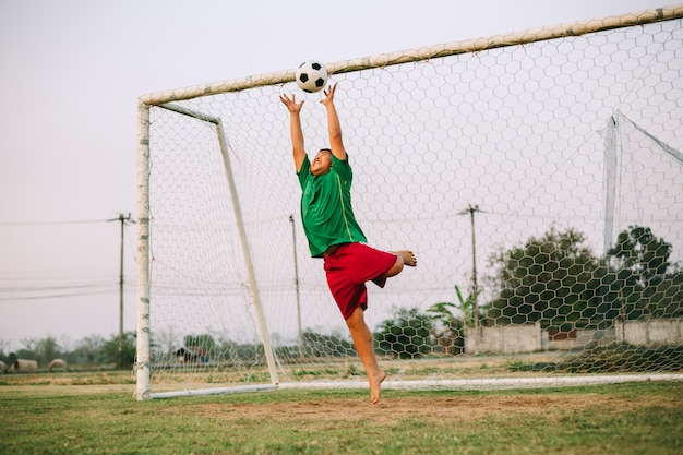 Sport picture of young boy playing soccer football as a goal keeper