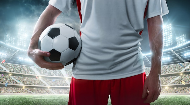 Sport. professional soccer player holding soccer ball on the stadium. close up