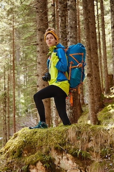 Sport, recreation and camping concept. full legth shot of active female hiker overcomes long distance, dressed in comfortable clothes
