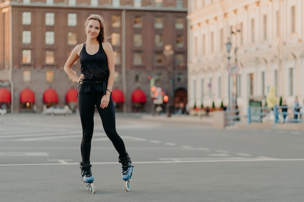 Sport and recreation concept. horizontal shot of active woman practices rollerblading poses on blades keeps hand on waist