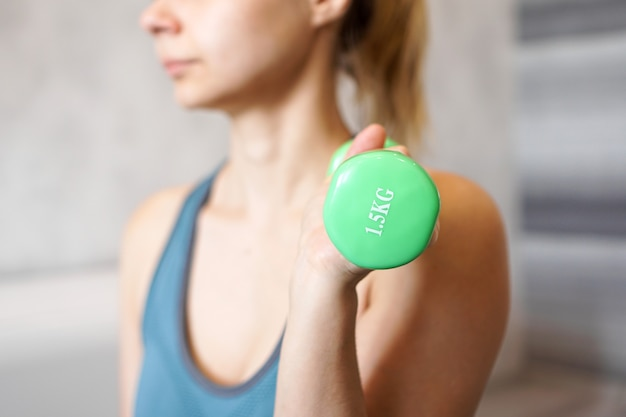 Sport and recreation concept - sporty woman hand with light green dumbbell
