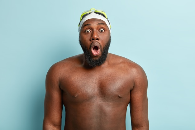 Sport, recreation and ethnicity concept. overwhelmed dark skinned male swimmer looks surprised with bated breath, has swimming goggles on forehead, swims in pool has naked strong body
