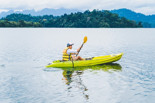 Sport and recreation. young man enjoy vacation kayak in cheow lan lake, thailand