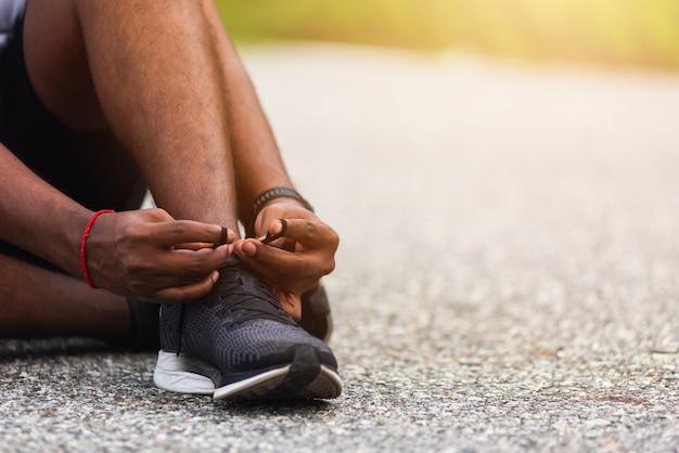 ジョギングの準備をしているランニングシューズを試して靴ひもに座っているスポーツランナー黒人男性