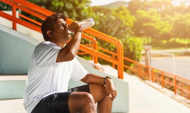スポーツランナーの黒人男性が実行した後彼はボトルから水を飲むアスリートヘッドフォンを着用します。