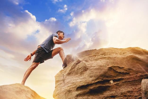 크로스 컨트리 트레일 실행에서 스포츠 실행 남자 바위 산 길에서 점프