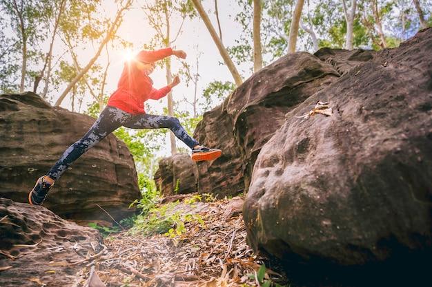크로스 컨트리 트레일 실행에서 스포츠 실행 중인 여자는 바위 산 경로에 점프