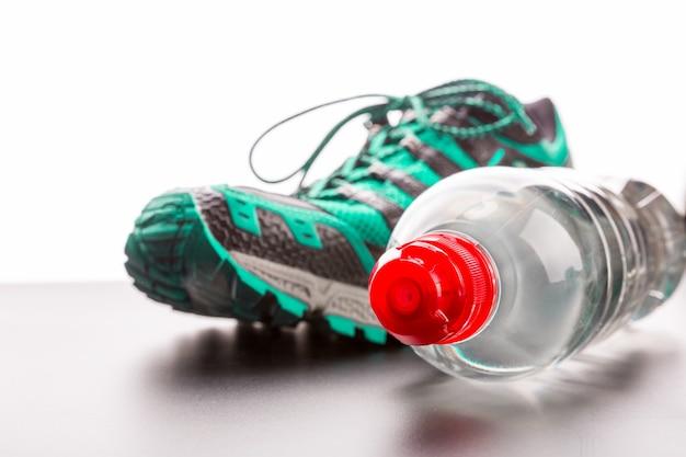 スポーツシューズと水のクローズアップのボトル