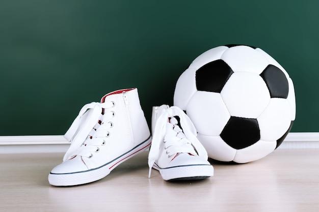 Спортивная обувь и футбольный мяч на фоне доски