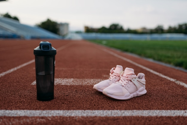 Sport shoes and bottle of water on stadium, nobody. running or fitness training concept, healthy lifestyle