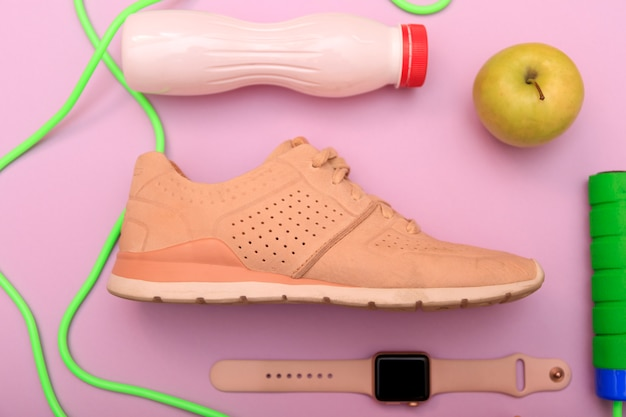 Sport shoes, dumbbells and skipping rope on pink