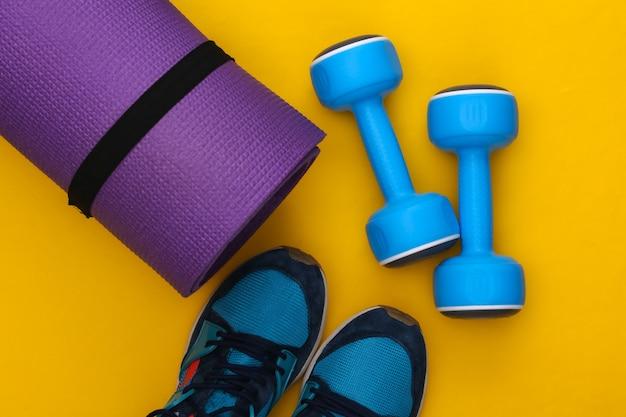 노란색 배경에 스포츠 신발, 피트니스 매트, 아령. 건강한 라이프 스타일, 피트니스 훈련. 평면도. 플랫 레이