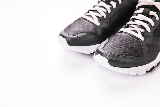 白で隔離されるスポーツの靴