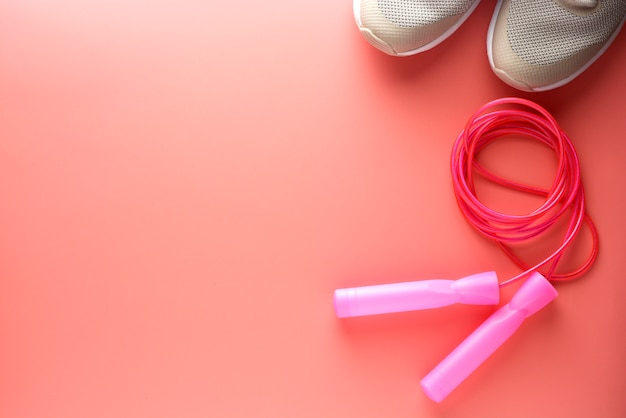 Sport shoes and jumping rope over pink background