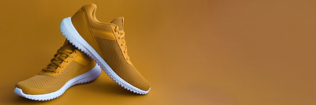 Sport shoes on mustard color wall