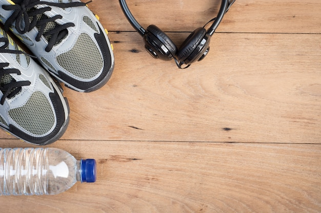 Sport shoes, sneaker and bottle of water on wooden background