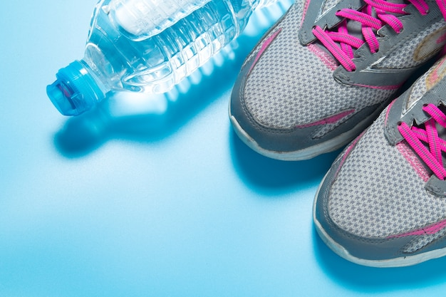 Sport shoes and water bottle on blue background with copyspace.