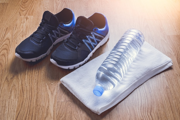 Sport shoes, water, towel on wooden background