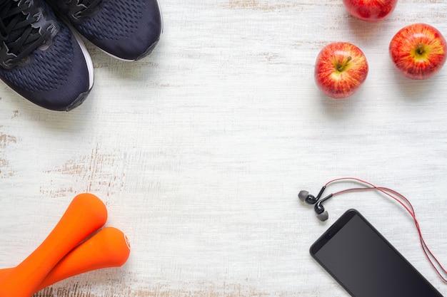 Спортивные шоты, гантели, смартфон и яблоки на гранж белой древесине