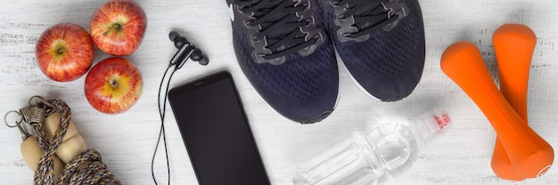 Sport shotes, dumbbells, smartphone and apples on grunge white wood