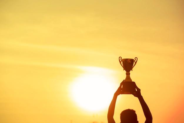 スポーツシルエットトロフィーは、プロが挑戦した優勝者の優勝トロフィーを手にした最高の男の手です。