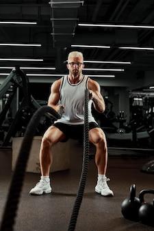 스포츠. 체육관에서 전투 로프와 함께 운동하는 강한 남자. 체육관에서 전투 로프 운동을 하는 선수. 극적인 스포츠 배경입니다.