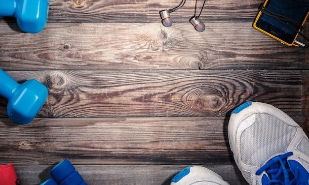 나무 탁자에 있는 스포츠 물건, 꼭대기. 텍스트, 로고 또는 다른 것을 위한 빈 공간이 있는 나무 테이블 중앙의 밝은 점.