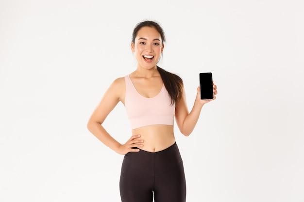 Концепция спорта, технологий и активного образа жизни. возбужденная жизнерадостная азиатская спортсменка, бегунья, показывающая свой лучший результат в приложении для смартфона, демонстрирует экран мобильного телефона с приложением для тренировки.
