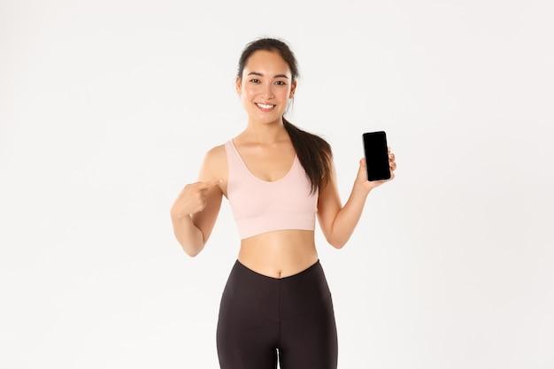 Концепция спорта, технологий и активного образа жизни. довольная улыбающаяся азиатская фитнес-девушка, привлекательная спортсменка, указывающая пальцем на экран смартфона, рекомендует мобильное приложение для отслеживания тренировок.