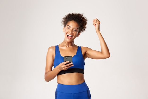 Sport and technology concept. attractive african-american female athelte achieve goal in worout app