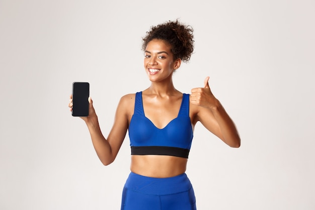 Sport and technology concept. young healthy african-american fitness woman showing thumbs-up and