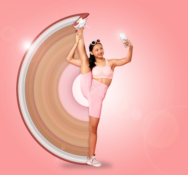 Спорт девушка-подросток поднимает гибкую ногу к голове, используя смартфон для селфи-фотосессии. азиатская молодежная спортсменка в пастельных розовых тканевых штанах для фитнеса на розовом фоне в полный рост
