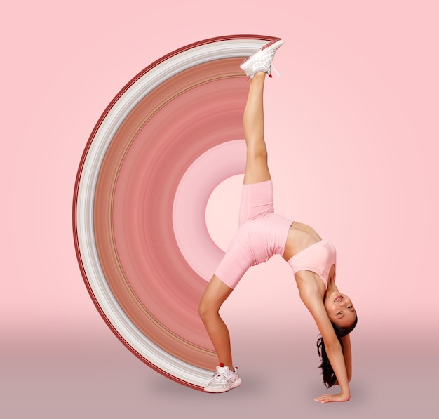 Sport teenager girl stretch lift up her flexible leg, do fashion poses. 12-15 years old asian youth athlete kid wear pastel pink fitness cloth pants over pink background full length
