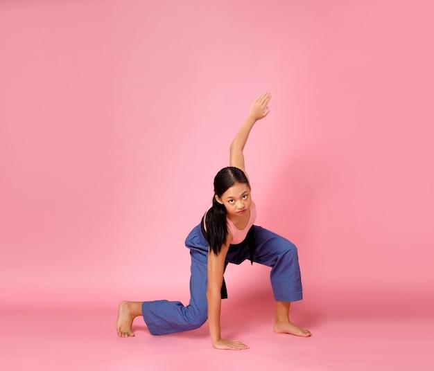 スポーツティーンエイジャーの女の子は、高台から着陸するときに地面に触れ、ファッションポーズをします。 12〜15歳のアジアのユースアスリートの子供は、ピンクの背景の全長にパステルピンクのフィットネスクロスパンツを着用します