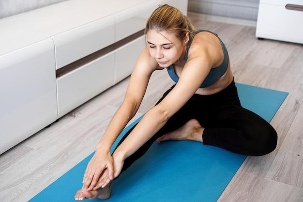 스포츠, 교육 및 라이프 스타일 개념-거실에서 집에서 파란색 요가 매트에 다리를 스트레칭하는 여자